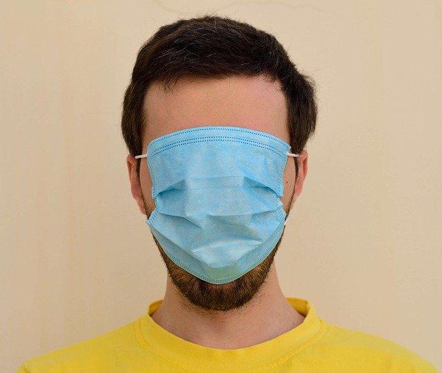 Mann mit Nasen- Mundmaske komplett über das Gesicht gezogen.