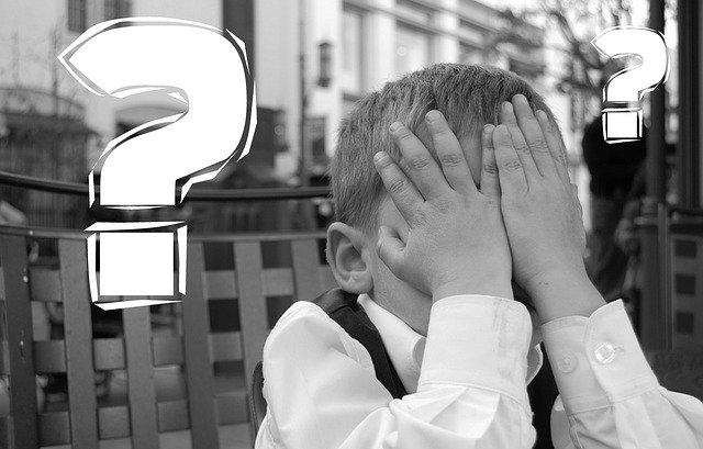 Kind schlägt Hände vor die Augen, Fragezeichen schweben um den Kopf